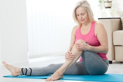 woman working on at home holding knee