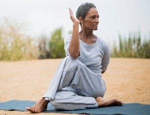 African American woman over 50 doing yoga stretch on mat