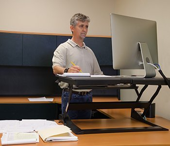 Man standing, using a desk.