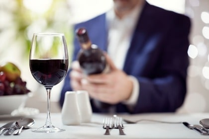 businessman reading the list of wine ingredients on bottle label with glass of red wine in foreground