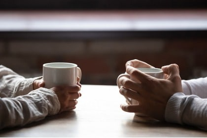 conversation-woman-and-man-holding-cups-of-coffee-on-table