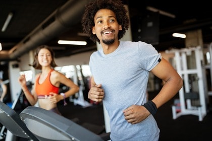 fit-young-man-and-woman-exercising-on-a-treadmill-in-gym