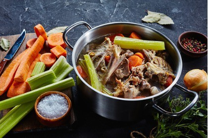 cooked-chicken-bone-broth-with-vegetables-and-aromatic-herbs-around-pot