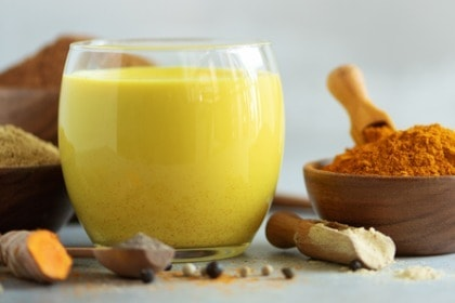turmeric golden milk with turmeric root and bowl of ground turmeric powder commonly used in Ayurvedic medicine