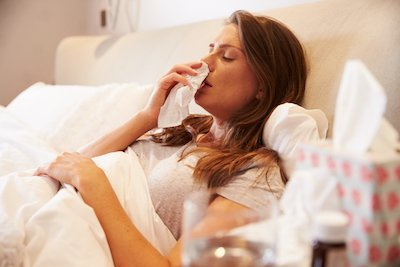 Woman Sitting in Bed with a cold Suing Tissues