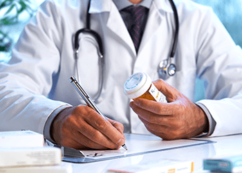 Doctor Writing Prescription with Pill Bottle in Hand