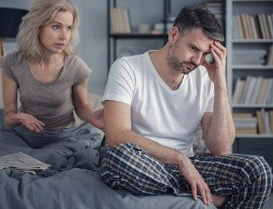 unhappy man and concerned wife in bedroom